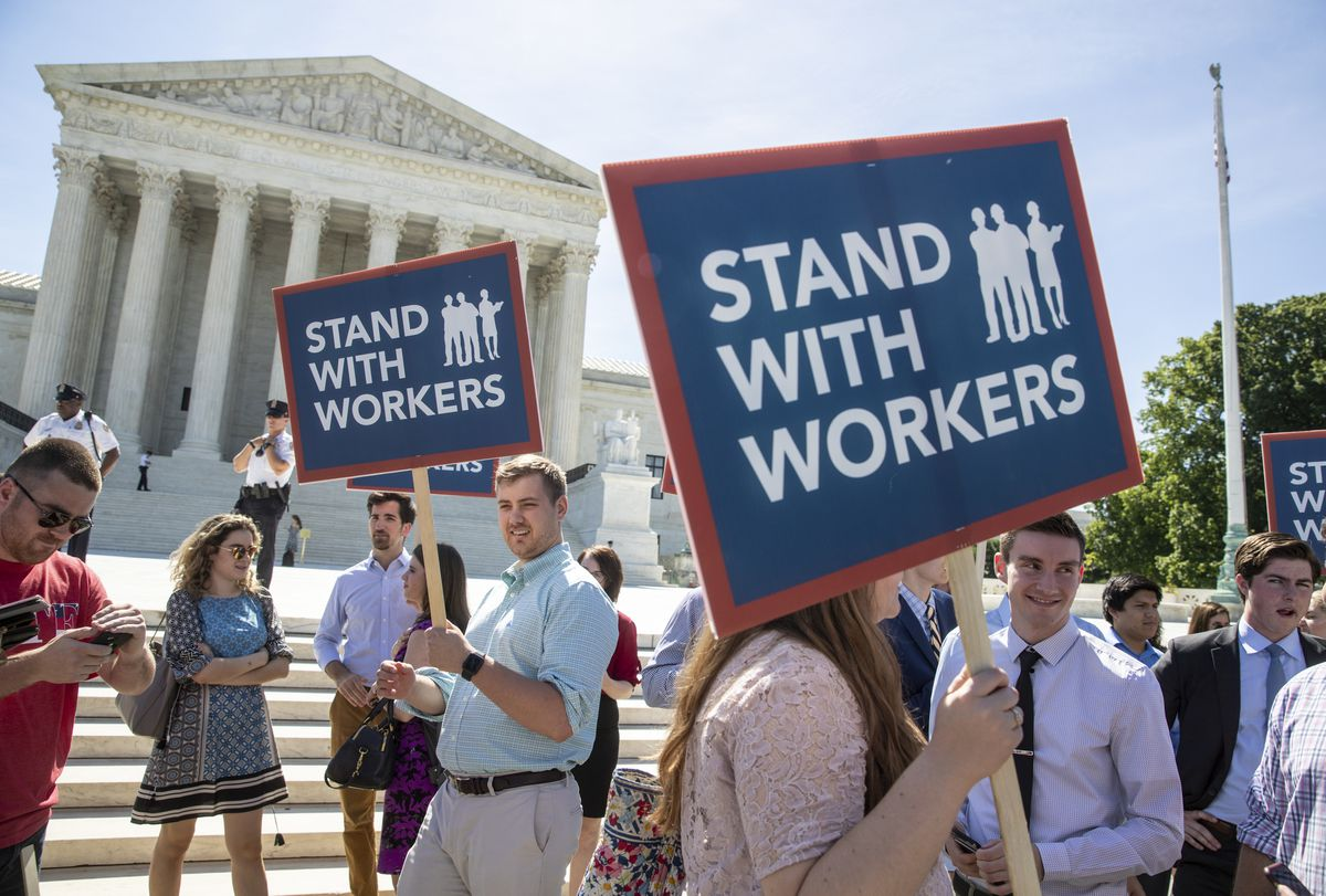 In this Monday, June 25, 2018 photo, people gather at the Supreme Court awaiting a decision in an Illinois union dues case, Janus vs. AFSCME, in Washington. The Supreme Court says government workers can't be forced to contribute to labor unions that represent them in collective bargaining, dealing a serious financial blow to organized labor.(AP Photo/J. Scott Applewhite)