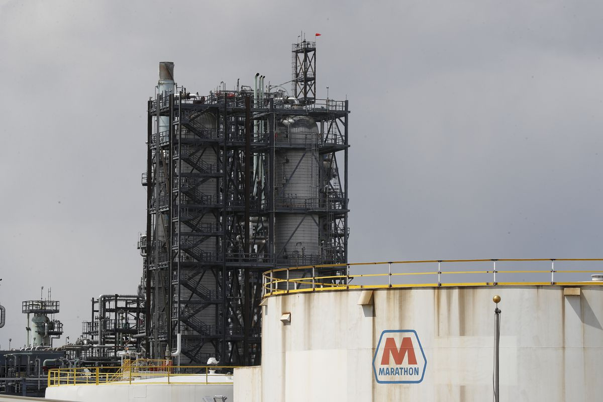 FILE - In this April 21, 2020, file photo storage is shown at the Marathon Petroleum Corp. refinery in Detroit. Thousands of oil and gas operations, government facilities and other sites won permission to stop monitoring for hazardous emissions or otherwise bypass rules intended to protect health and the environment because of the coronavirus outbreak, The Associated Press has found. (AP Photo/Paul Sancya, File)
