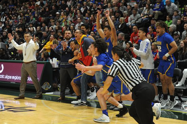 The Barrow High Whalers and former Whaler Kamaka Hepa explode off the bench at the end of the championship game of the 3A boys Alaska State basketball tournament at the UAA Alaska Airlines Center in Anchorage, Alaska on Saturday, March 24, 2018. Barrow won the championship defeating Grace Christian 65-52. (Bob Hallinen / ADN)