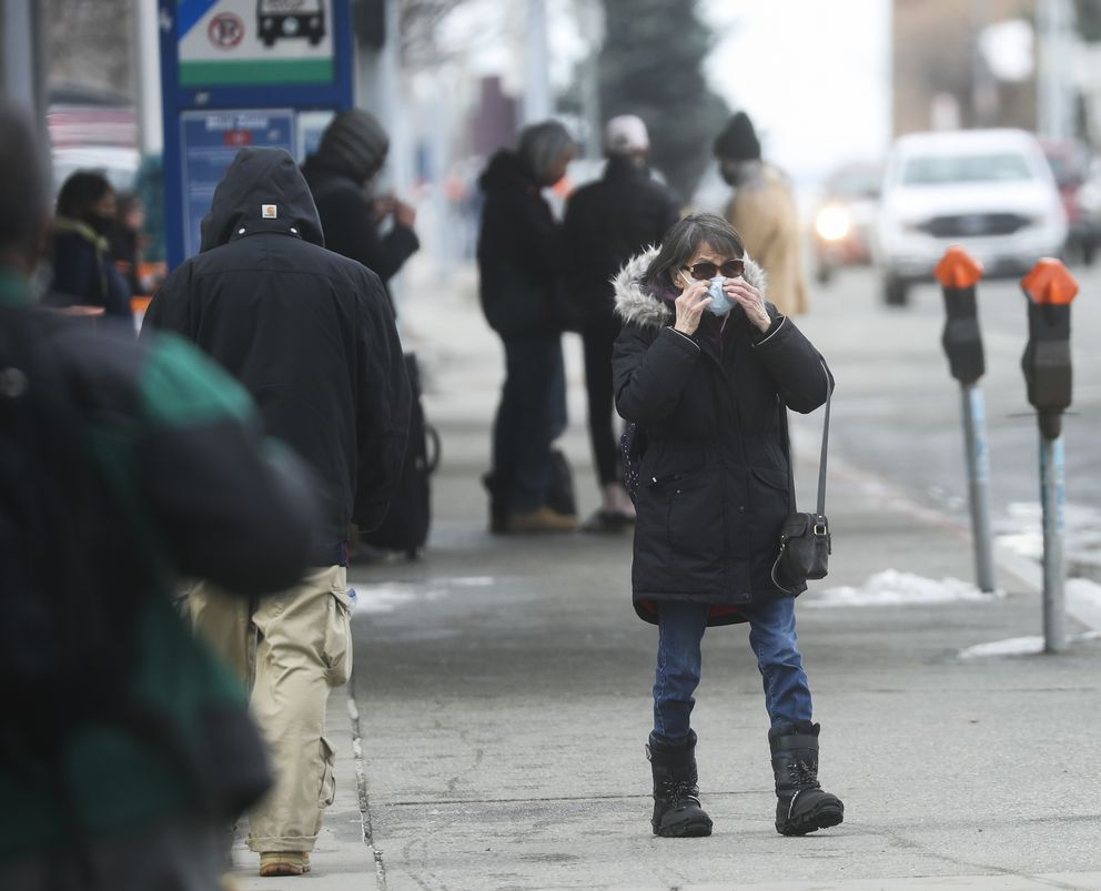 A woman adjusts her face mask near the bus stop on W. Sixth Avenue in downtown Anchorage on Monday, April 12, 2021. (Emily Mesner / ADN)