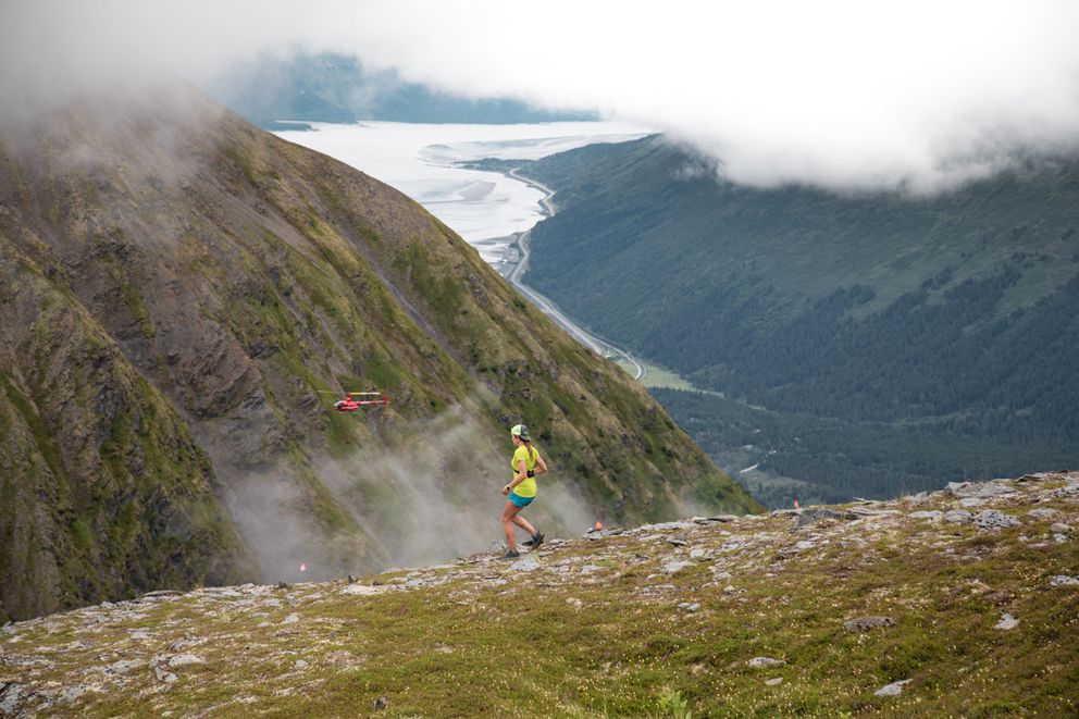 A helicopter and a runner are dwarfed by their surroundings at the Alyeska Cirque race on Sunday, Aug. 5, 2018.