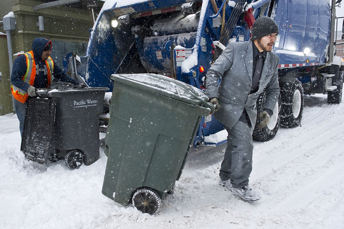 FILE: In this Dec. 7, 2016, file photo, Charlie Gallant, right, empties garbage containers with Brian Felipe, left, for Pacific Waste on South Franklin Street in Juneau. (Michael Penn/The Juneau Empire via AP, File)