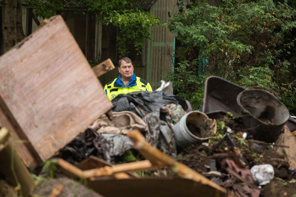 Richard Fern, the municipality's lead land use enforcement officer, observes a crew clearing debris from a nuisance property in South Anchorage on Wednesday. (Loren Holmes / ADN)