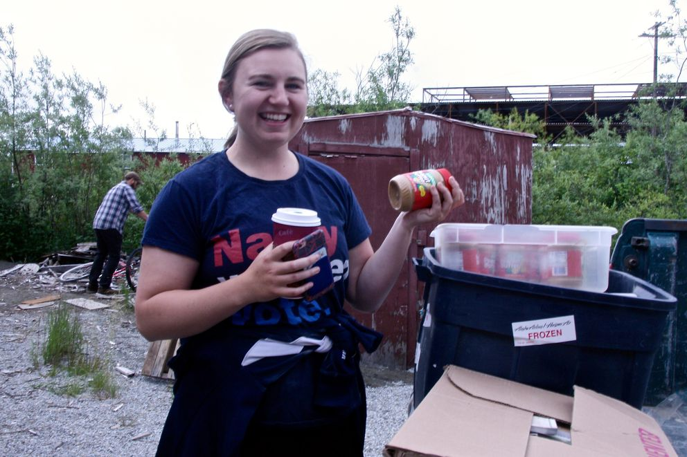Cece Franko, a Jesuit volunteer who has signed up for a second year of service, holds up a jar of peanut butter to show some of what she is moving from the old house to the new one. The donated peanut butter expired in 2014 but still is good for cooking, she said. (Lisa Demer / Alaska Dispatch News)