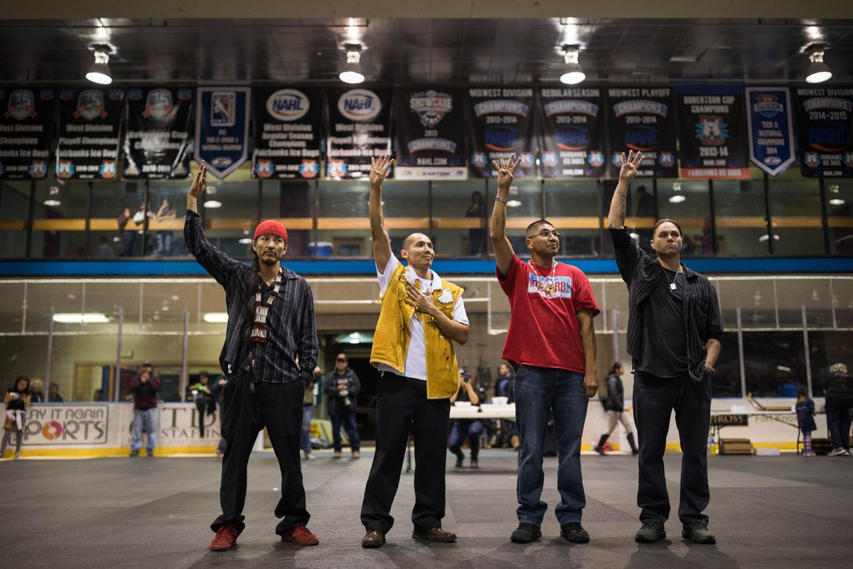 The Fairbanks Four, from left, George Frese, Marvin Roberts, Eugene Vent and Kevin Pease, raise four fingers, displaying the symbol of their struggle, during a potlatch held in their honor at the Big Dipper arena in Fairbanks on Oct. 19, 2016. (Loren Holmes / ADN)