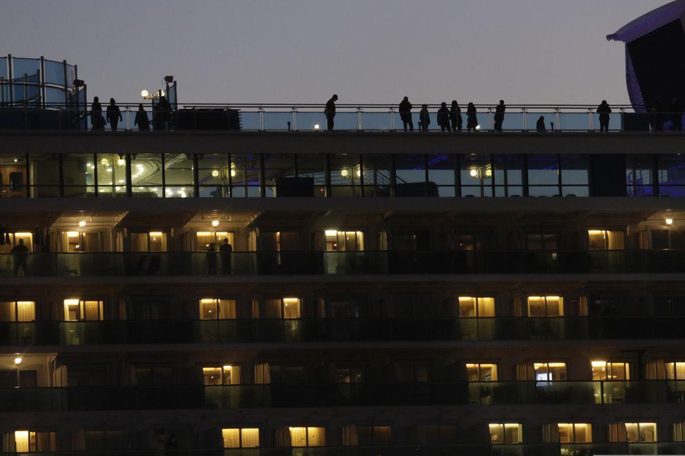 Tourists quarantined on the Diamond Princess cruise ship get some fresh air on the top deck of the ship Thursday, Feb. 13, 2020, in Yokohama, near Tokyo. (AP Photo/Jae C. Hong)