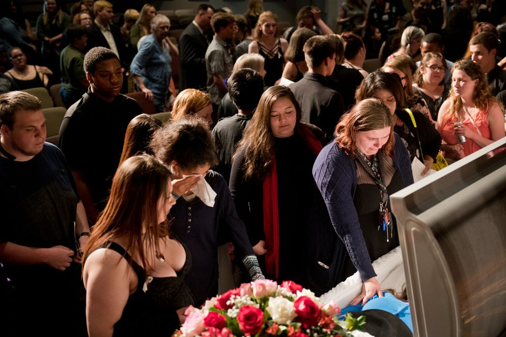 """Friends and family visit the casket of Cynthia Hoffman at the conclusion of her funeral. Hundreds gathered at Faith Christian Community church on Wisconsin street for Cynthia Hoffman's funeral Thursday afternoon, June 13, 2019. State prosecutors say Hoffman, a Service High School graduate, was killed at the Thunderbird Falls trailhead in Chugiak on June 2 by two Anchorage teenagers, Denali Brehmer and Kayden McIntosh.On Thursday, dozens of motorcycles escorted the hearse carrying Hoffman to the service. Tim Hoffman, Cynthia's father, rode his motorcycle behind it. During opening remarks, Tim Hoffman asked the audience to try to keep the remembrance of his daughter joyful. """"I don't want this reunion to be a sadness. I want it to be a new birth of my daughter,"""" he said. Several friends and family members shared memories and shared songs of Cynthia. Five teenagers have been charged in her death: Brehmer, 18, McIntosh, 16, Caleb Leyland, 19, and two minors who haven't been identified. Tim Hoffman said he planned to attend all the court hearings. """"I have a court appearance at 8:30 tomorrow morning at downtown jail,"""" he told the audience at the funeral. """"And excuse my French, but I'm going to send them all to hell."""" (Marc Lester / ADN)"""