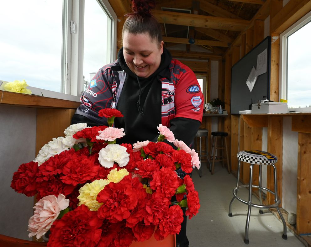 Amy Johnson handed out carnations to mothers while at the ticket booth on opening day of Alaska Raceway Park on Mother's Day, Sunday, May 9, 2021. (Bill Roth / ADN)