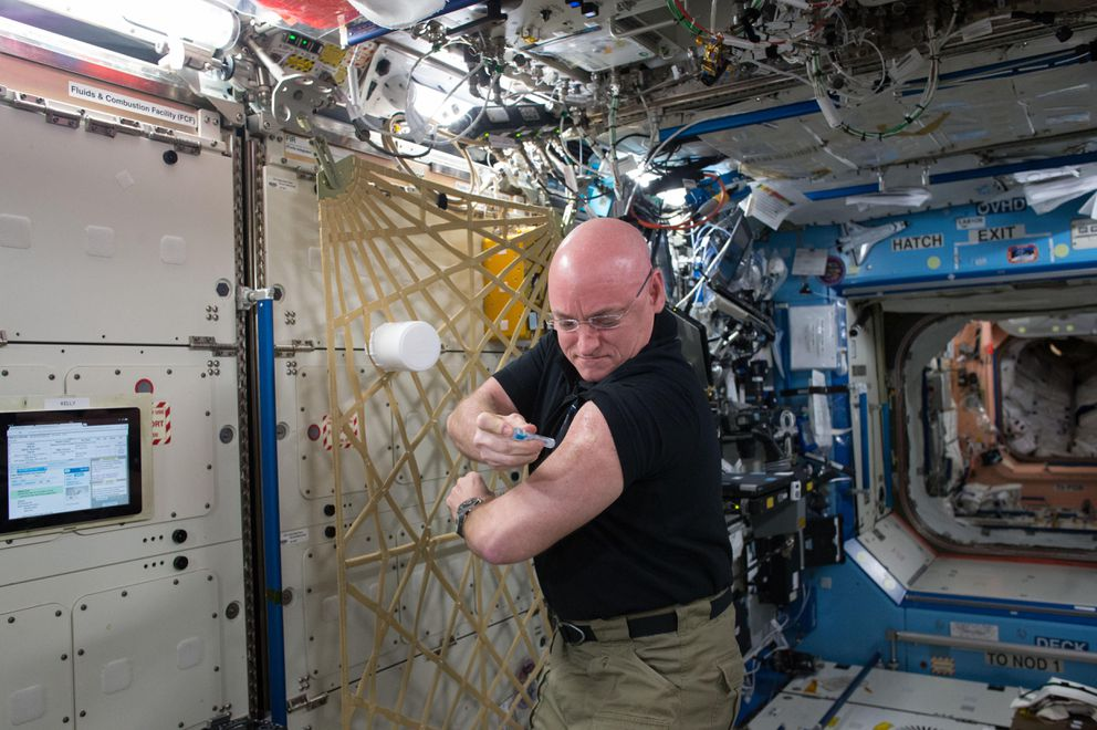 NASA astronaut Scott Kelly gives himself a flu shot for a study on the human immune system. NASA