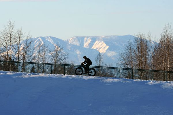 A cyclist pedals past Sleeping Lady up towards the chalet and parking lot on Wednesday afternoon, March 22, 2017, in Kincaid Park. (Erik Hill / Alaska Dispatch News)