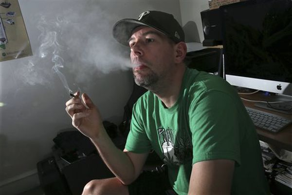 Former U.S. Marine Mike Whiter smokes marijuana before he starts editing a video project at his home in Philadelphia.