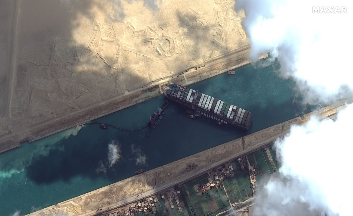 This satellite image from Maxar Technologies shows the cargo ship MV Ever Given stuck in the Suez Canal near Suez, Egypt, Friday, March 26, 2021. A maritime traffic jam grew to more than 200 vessels Friday outside the Suez Canal and some vessels began changing course as dredgers worked frantically to free a giant container ship that is stuck sideways in the waterway and disrupting global shipping. (©Maxar Technologies via AP)