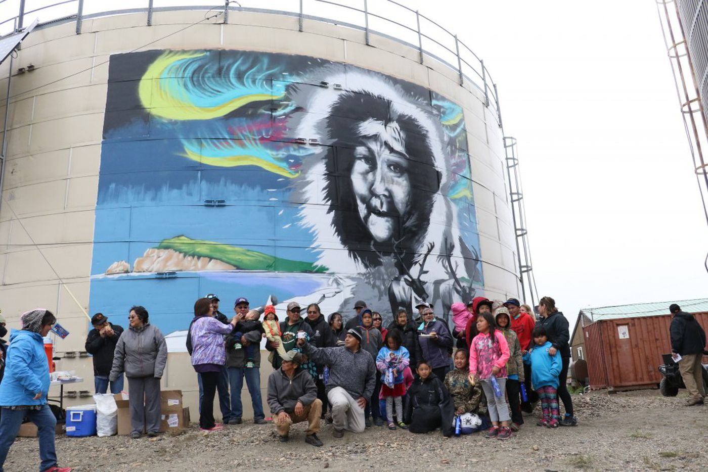 The Water is Life mural in Deering, Alaska, with community collaborators celebrating completion. (Photo by Bailey Berg / Alaska Dispatch News)