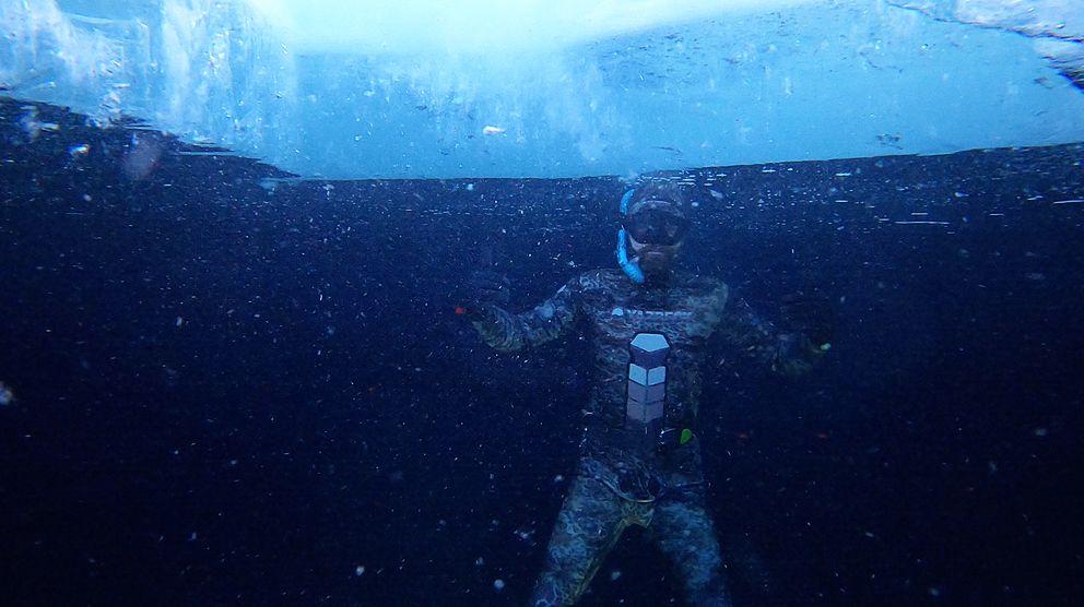 Jarod Powell freedives under ice that formed on Rabbit Lake on Sunday, Jan. 3, 2021. (Photo courtesy of Alex Fancher)