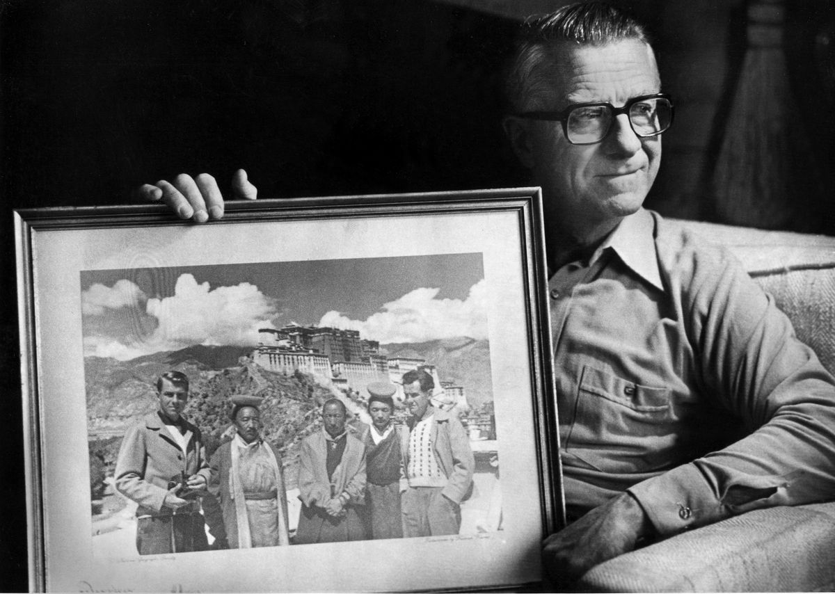 Lowell Thomas, Jr. holds a photograph showing him, far left, and his father, far right, during their 1949 trip to Tibet. (Anchorage Daily News archive 1983)