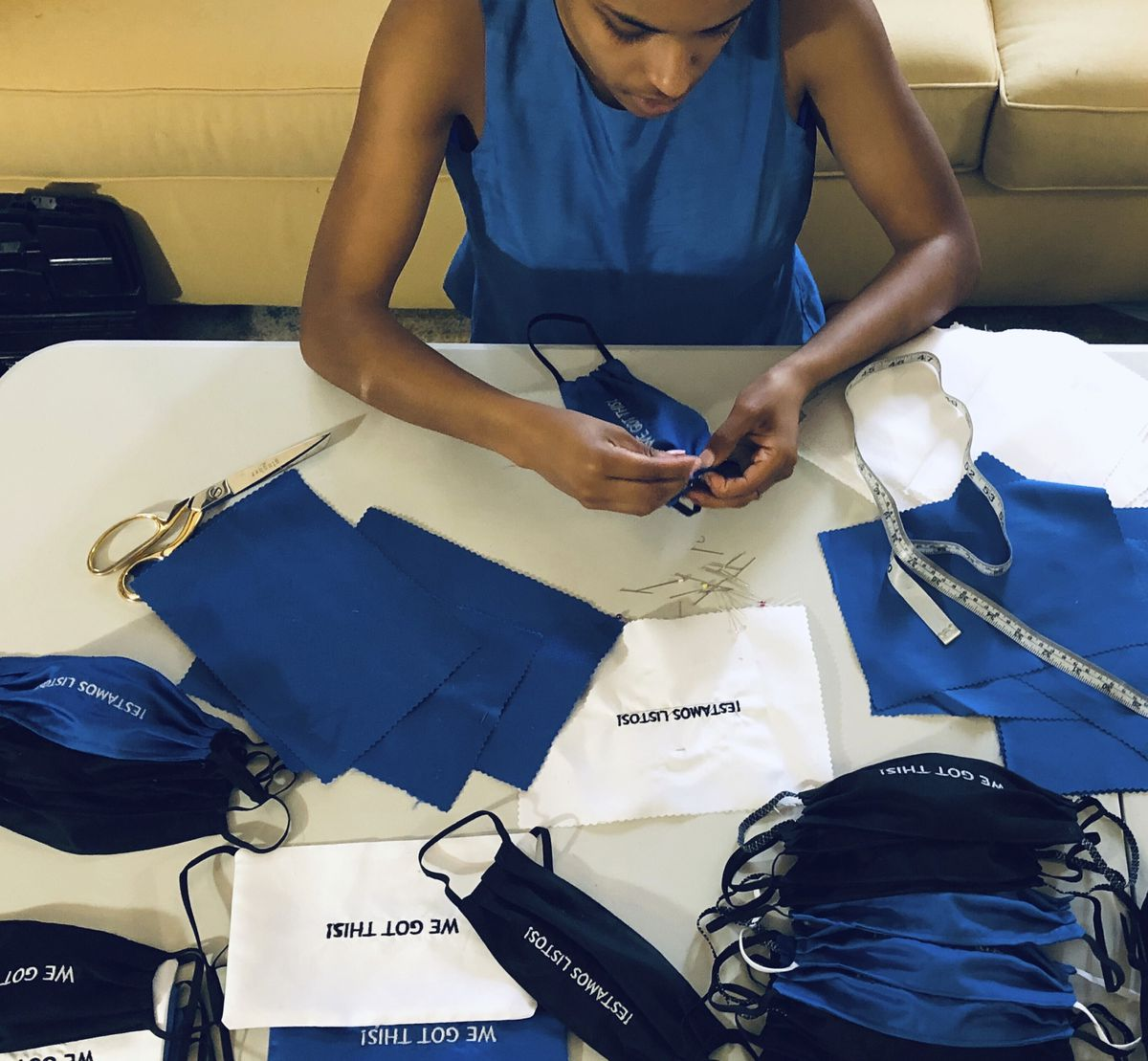 In this Sunday, March 22, 2020, photo, provided by Christina Hunter, Briana Danyele sews cloth face masks that say