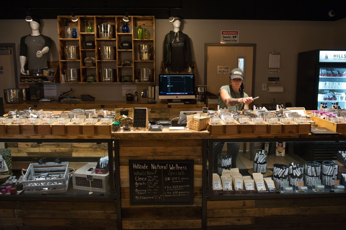 Jamie Bridges, assistant store manager, works behind the counter on April 30, 2018, at Hillside Natural Wellness marijuana store in South Anchorage. (Marc Lester / ADN)