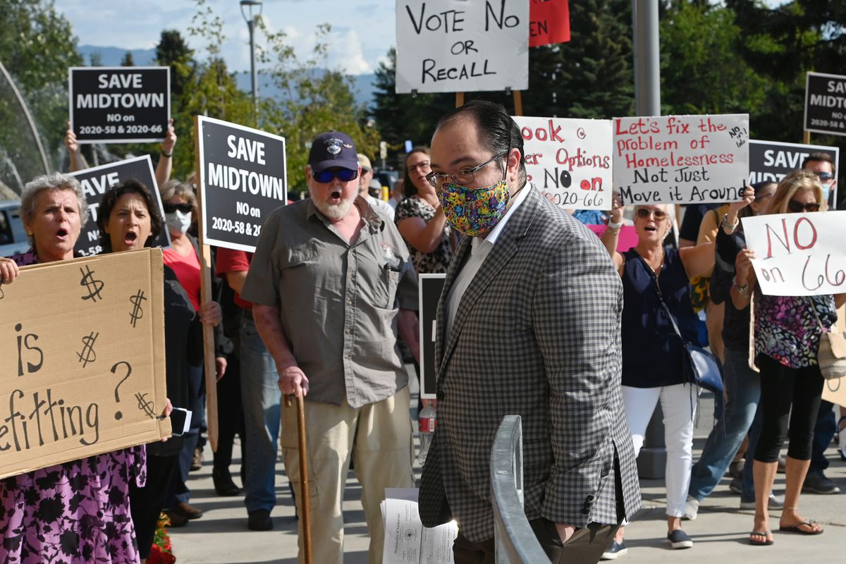 Anchorage Assembly chair Felix Rivera walks past protesters chanting