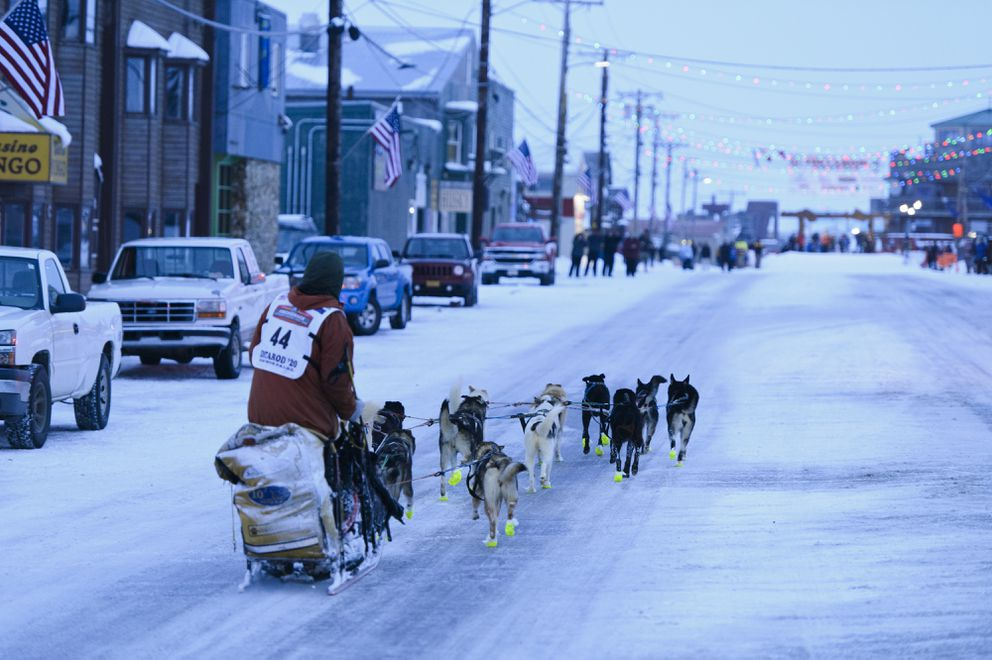 Brent Sass drives his team down Front Street in Nome on March 18, 2020, as he finishes the Iditarod Trail Sled Dog Race in fourth place. (Marc Lester / ADN)