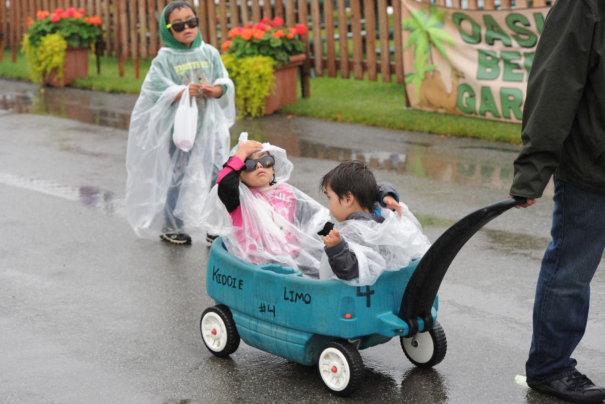 Jazlynn Williams, 3, center, and Blake Williams, 2, adjust their hoods as a light drizzle greeted fair goers on the opening day of the Alaska State Fair in Palmer on Aug. 25, 2016. Hayden Williams, 6, follows from behind. (Bill Roth / ADN archive)
