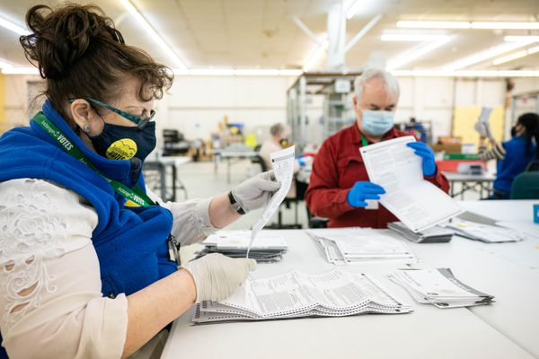 Election workers Jean Sondrud, left, and Marvin Cox unfold ballots so they can be scanned on Wednesday, April 7, 2021 at the Municipality of Anchorage election center. The municipality is continuing to count ballots a day after election day. (Loren Holmes / ADN)