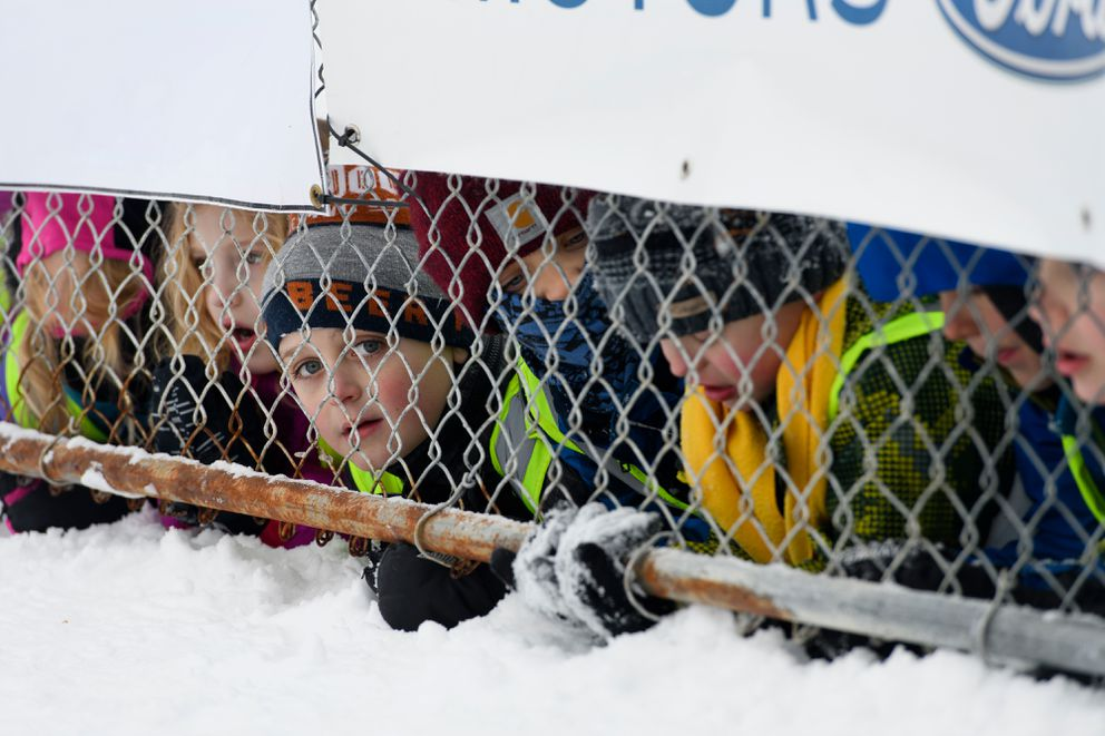 Students from Spruce Tree Montessori School in Fairbanks peek under banners on a chain link fence to watch as musher Hans Gatt is interviewed. Hans Gatt, of Whitehorse, Yukon, arrived in Fairbanks to place second in the Yukon Quest International Sled Dog Race. (Marc Lester / ADN)