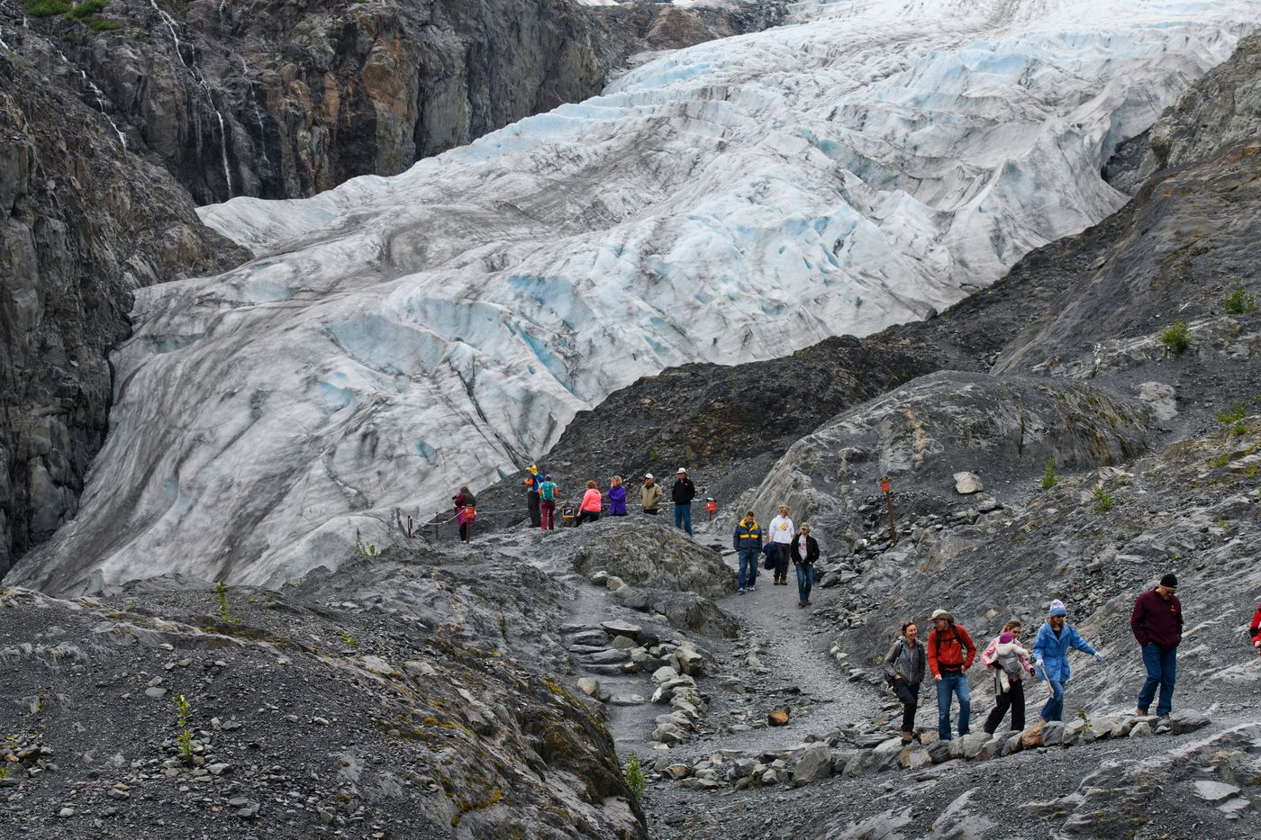 Visitors walk to and from an Exit Glacier overlook in Kenai Fjords National Park on June 23, 2018. One-year-old Clara Andrews is carried by her mother, Rachel Andrews, third from right. (Marc Lester / ADN)