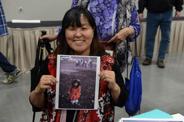 Elvina Lincoln holds a photograph of herself as a 3-year old in Anaktuvuk Pass, AK at the Anchorage Museum booth at AFN. Alaska Federation of Natives Convention attendees looked at photographs at the Anchorage Museum booth to try and identify people and places in them at the Dena'ina Center in Anchorage, AK on Thursday, Oct 18, 2018. The museum has been bringing recent photo donations to the convention for the past 6-years. (Bob Hallinen / ADN)