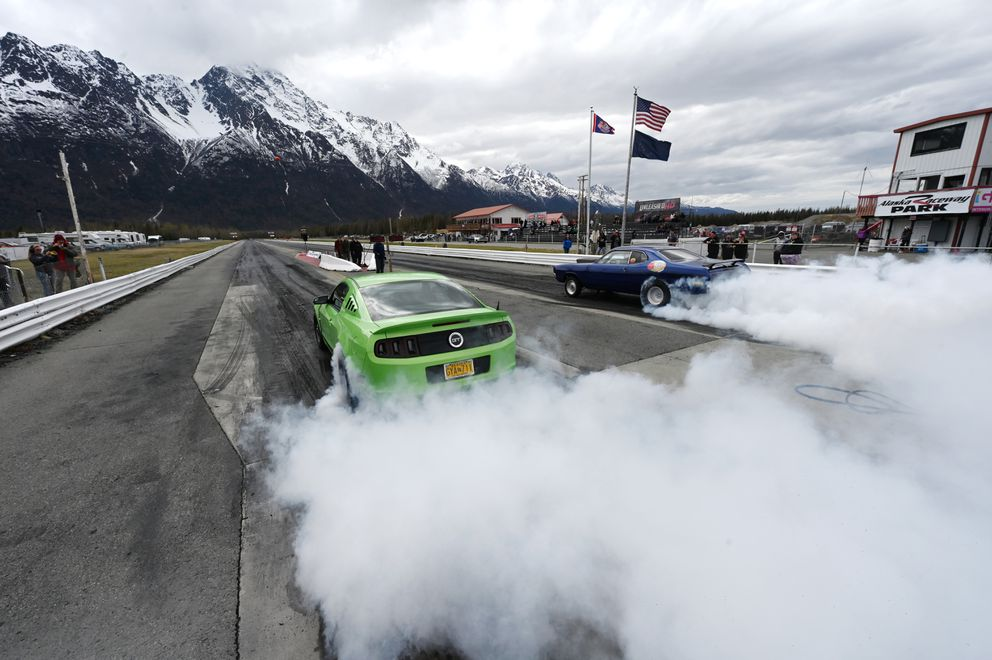 Joseph Nowell of Fairbanks in his 2014 Ford Mustang, left, and Bob Lee of Anchorage driving a 1972 Dodge Demon perform burnouts prior to competing in the Hunison Cup Drag Race on the opening day at Alaska Raceway Park on Mother's Day, Sunday, May 9, 2021. Nowell broke out with a time of 10.46 seconds in the quarter mile at 131.28 m.p.h. 'My car decided to run faster than it has all day, ' said Nowell. Lee advanced to the second elimination round on a 10.62 second pass at 110 m.p.h. (Bill Roth / ADN)