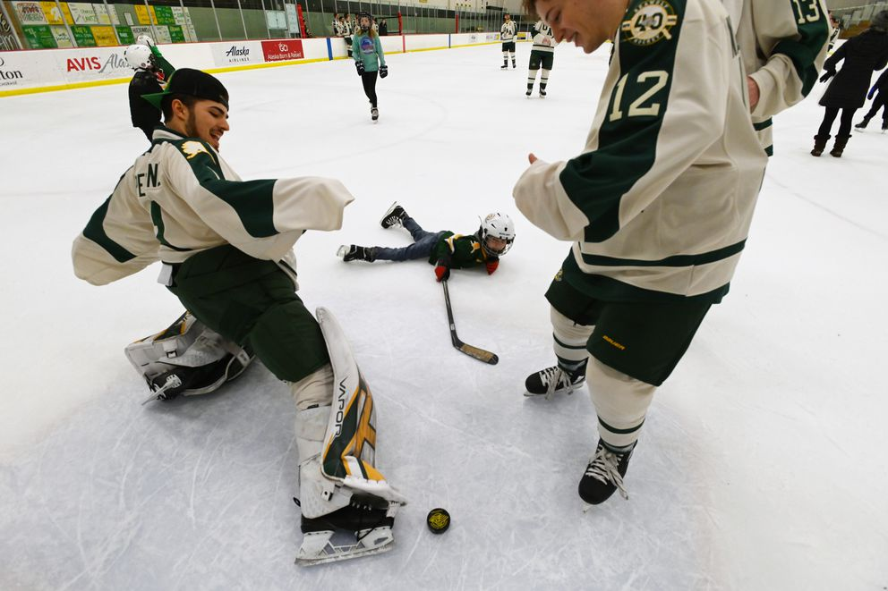 6-year-old Miles O'Toole takes a shot against UAA goalie Brandon Perrone and right winger Zach Nazzarett, both freshman, during the Skate with the Seawolves event after Sunday's game. (Bill Roth / ADN)