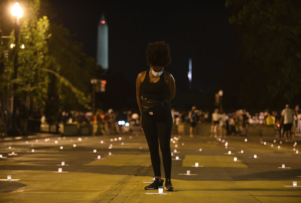 Activist Allison Lane, 34, stands amid candles at Black Lives Matter Plaza in Washington, D.C., during a July vigil to mark the death of civil rights activist and congressman John Lewis, D-Ga. Photo for The Washington Post by Astrid Riecken
