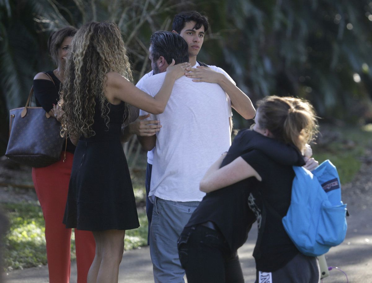 Parents and students gather outside the Marjory Stoneman Douglas High School during a shooting incident in Parkland, Fla., Feb. 14, 2018. Numerous fatalities were reported at this school about an hour northwest of Miami, and authorities reported that a suspect was in custody. (Saul Martinez/The New York Times)
