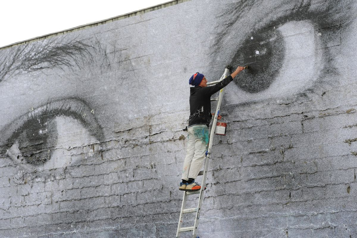 Artist James Temte touches up a wheat paste mural installation of a photograph by Michael Conti on a building next to the vacant lot where the Paradise Inn once stood in Spenard on Sunday, Sept. 22, 2019. (Bill Roth / ADN)