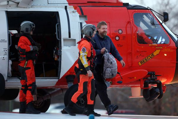 Louis Jordan, right, walks from the Coast Guard helicopter to the Sentara Norfolk General Hospital in Norfolk, Va., after being found off the North Carolina coast, Thursday, April 2, 2015. His family says he sailed out of a marina in Conway, South Carolina, on Jan. 23, and hadn't been heard from since.