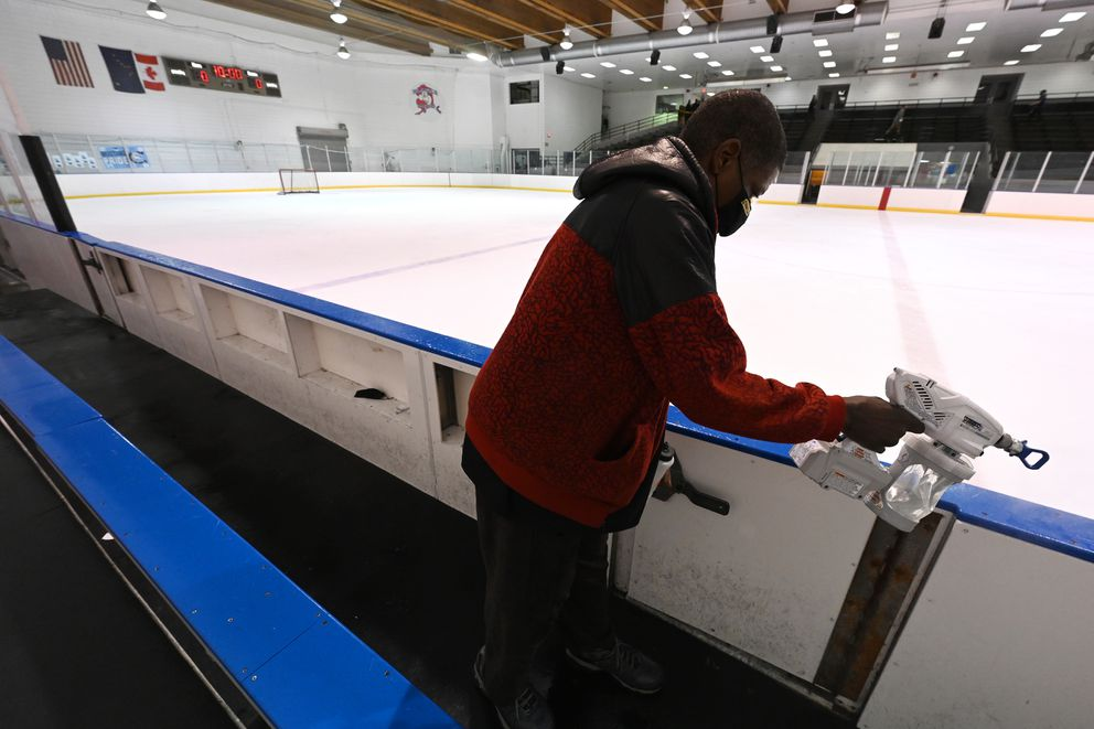 Shawn Felths disinfects the bench area between games Tuesday at the CIC hockey tournament. (Bill Roth / ADN)
