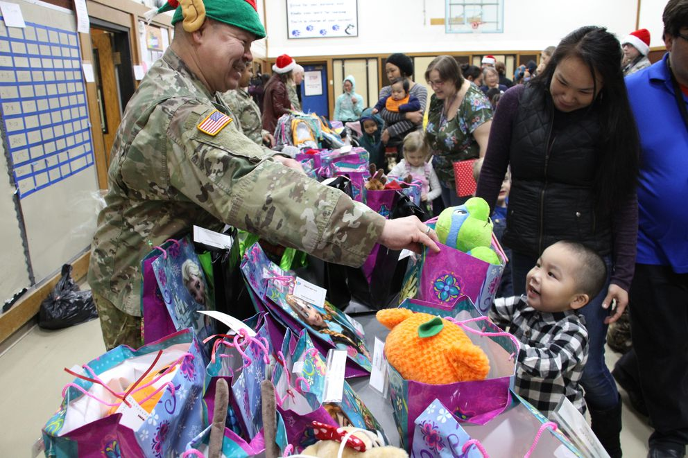 This Dec. 3, 2019, photo shows Alaska National Guard Staff Sgt. Joseph Sallaffie handing a gift bag to Corban Jimmy while Marlene Black looks on during Santa's visit to Napakiak. (AP Photo/Mark Thiessen)