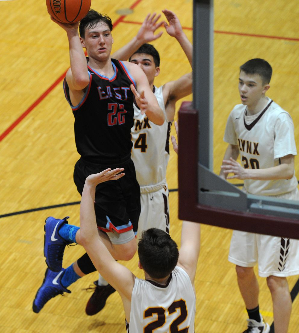 Eas'ts Moses Miller puts up a shot against Dimond defenders. (Bill Roth / Alaska Dispatch News)