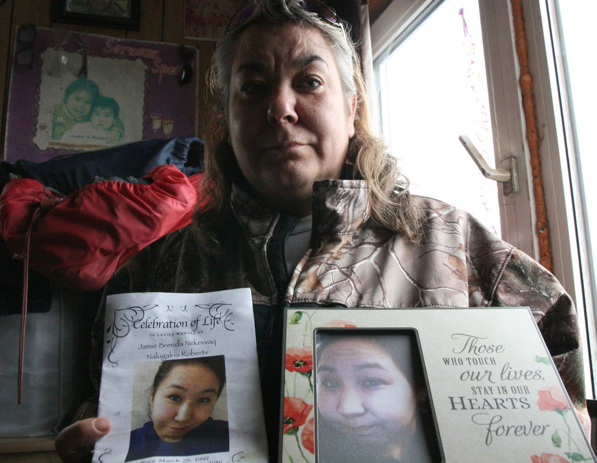 Phyllis Roberts of Quinhagak on Sept. 15, 2016, shows a photo of and the memorial service flier for her daughter, Jamie Brenda Roberts, who died a month earlier of a heroin overdose in the Southwestern Alaska village.