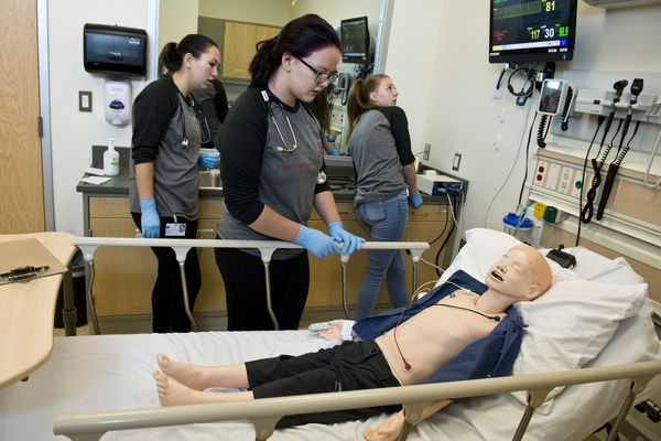"""From left, Maddy Carter, Natalie Waterhouse and Nadia Walluk tend to a simulated patient as instructors observe through mirrored window. Fifteen high school upperclassmen and recent graduates from around Alaska are participating in Anchorage Nurse Camp at UAA this week. The program is hosted by RRANN, Recruitment and Retention of Alaska Natives into Nursing, a part of UAA's school of nursing. Students are gaining some hands-on skills, such as giving injections, dressing wounds, checking vital signs and doing other simulated treatment on dummies. Annette Rearden, RRANN coordinator and a nursing professor, said the goal of the camp is to introduce students to the profession and encourage them to consider nursing as a career. Statewide, the program hopes to increase the number of Alaska Native nurses. Now, many places in both rural and urban Alaska, rely on traveling nurses who often work on a 13-week rotation. """"We are in a shortage, and we need culturally competent nurses to provide good care,"""" Rearden said. Kelly O'Brien, who recently completed her junior year at Bethel Regional High School, and Tina Conwell, of Kotzebue, were two students that tended to a dummy patient Wednesday morning in the Interprofessional Health Sciences Simulation Center. There they tended to a hypothetical situation involving a hypothermic child who had been lost in the woods. """"There's a lot of information that we've had to take in, but it hasn't really been stressful,"""" she said afterward. """"It's a lot of fun."""" Conwell said it was exciting to be part of the process, but nerve-wracking. """"It was like he was a real person and we're supposed to treat him like a real person, and that made me nervous,"""" Conwell said. Rearden said Alaska Native and American Indian nurses are far underrepresented in the profession, compared to the demographic makeup of the state. She hopes the camp will be one way to make a difference. """"We feel strongly that in the RRANN program, obviously, that if we can have that, t"""