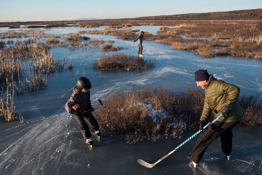 Jim Tuomi skates with his sons Jack, 9, left, and Marc, 11. Potter Marsh attracted ice skaters on November 5, 2018. (Marc Lester / ADN)