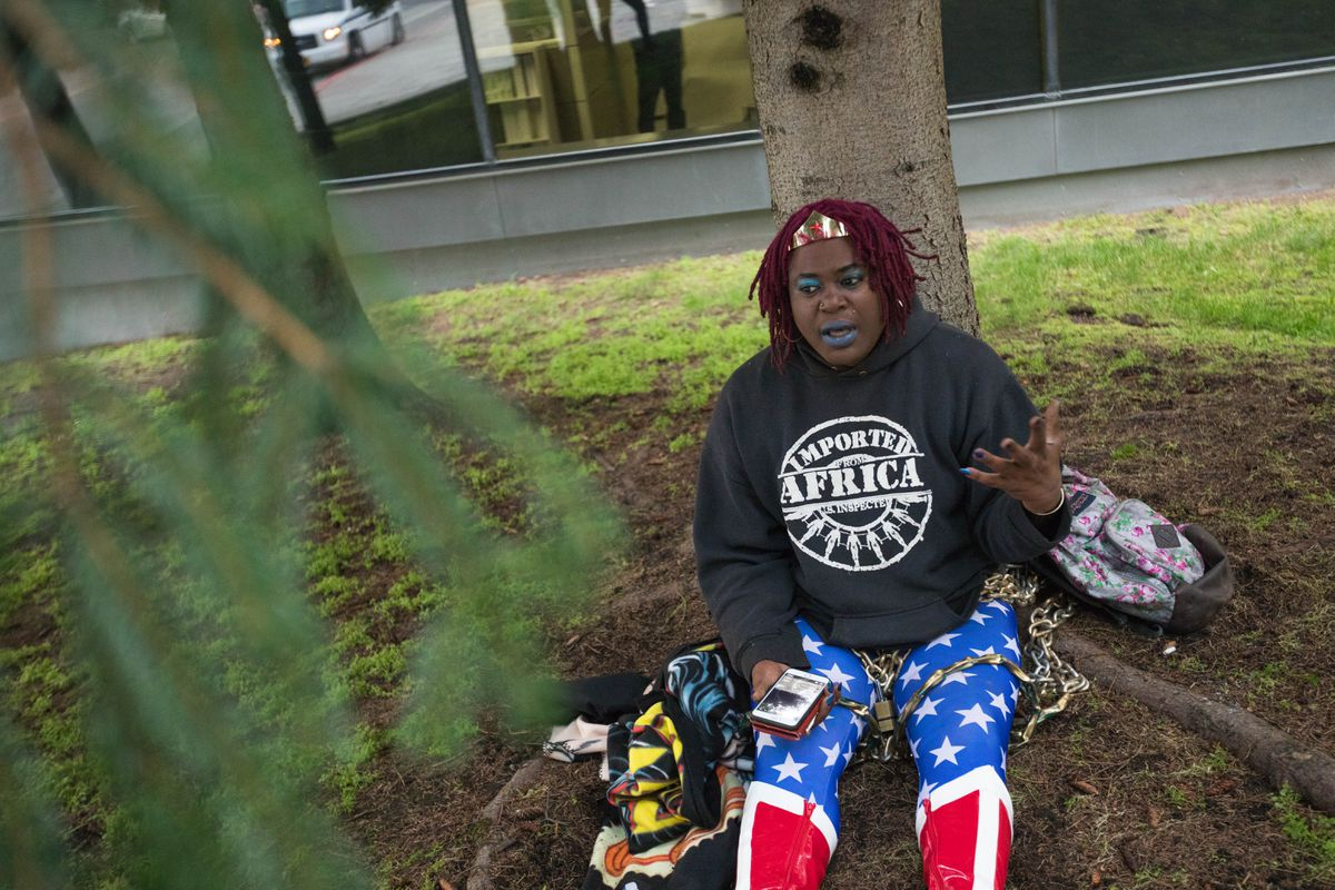 MoHagani Magnetek, a transgender woman, streams a Facebook live video as she is chained to a tree outside the federal building Sept. 7, 2017, in downtown Anchorage. Magnetek was protesting the treatment she received from Alaska State Troopers after she reported an assault. Magnetek says she was repeatedly misgendered by the trooper during a phone call and that her concerns were not properly investigated. (Loren Holmes / Alaska Dispatch News)