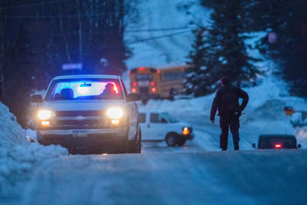 A police officer helps motorists stranded on the side of an icy Hillside Dr. early Thursday morning, Jan. 26, 2017. Freezing rain made roads extremely icy during the morning commute. (Loren Holmes / Alaska Dispatch News)