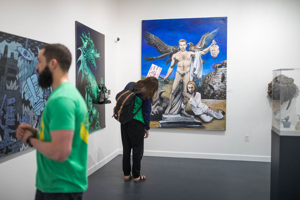 """UAA engineering student Delphine Dyer views professor Thomas Chung's painting """"Everything"""" at the UAA Kimura Gallery on Thursday. The painting, which features the severed head of Donald Trump, has generated some controversy and led to threats against Chung. (Loren Holmes / Alaska Dispatch News)"""