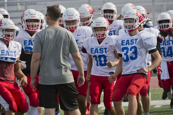 """Coach Jeff Trotter talks to his team. East High football gathered for its first regular season practice on Wednesday, July 31, 2019. Head coach Jeff Trotter said he's not running practice at full intensity yet, but other camps have helped. """"We're actually not to far off where we want to be, at least for this point,"""" Trotter said. The East T-Birds won the state championship last season. Trotter said he thinks his strategy of rotating players in and out of the game will help maintain some momentum heading into this season. """"We lost some really good talent, but the guys coming back (are) very experience because they have a lot of game time,"""" he said. East opens its season with a home game against Colony on August 16. (Marc Lester / ADN)"""
