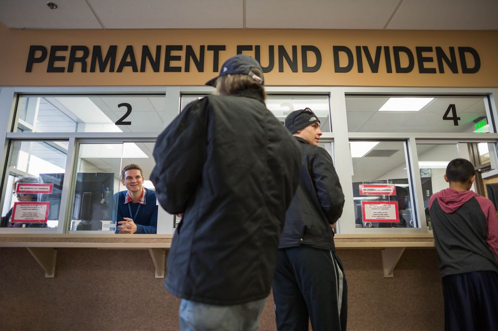 PFD Technician Shilo Franklin, left, helps people process their Permanent Fund Dividend applications at the downtown Anchorage PFD office on Thursday, March 31, 2016. (LOREN HOLMES / ADN archive 2016)