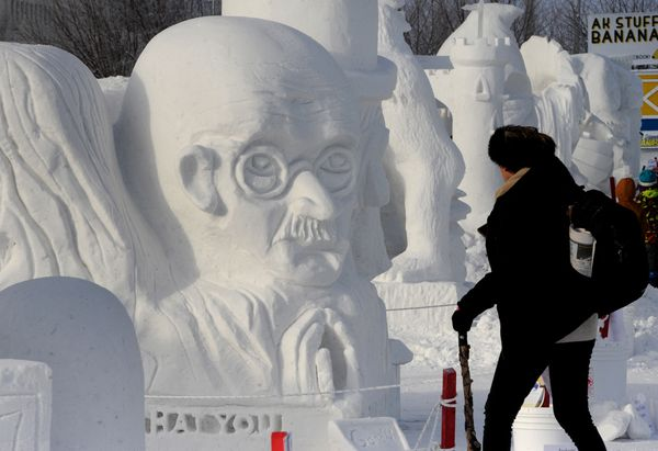 """Marie Tax of Maryland views a snow sculpture carved by students from Anchorage Waldrof School that featured busts of Gandhi, Lincoln, MLK and Katie John with an inscription, """"Be the change that you wish to see in the world,"""" that was one of the winning school entries at the Alaska State Snow Sculpture Championship during the Fur Rondy winter festival on Sunday, Feb. 25, 2018. (Bill Roth / ADN)"""