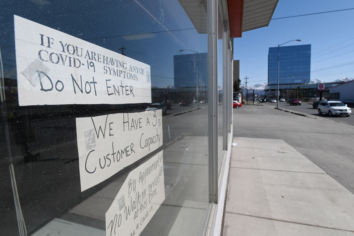 Bev's Dog Grooming on Northern Lights Boulevard put up signs on Monday, April 27, 2020, as they prepared to reopen for business during the coronavirus pandemic. (Bill Roth / ADN)