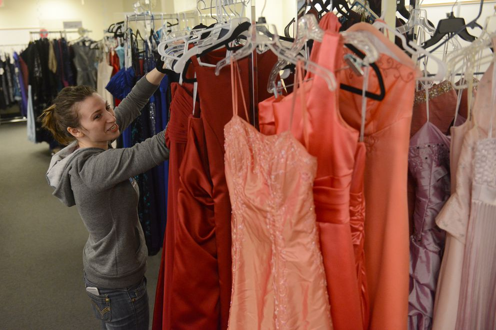 Anna Grant hangs up dresses at Becca's Closet in Anchorage, AK on Saturday April 21, 2018. Becca's Closet, located at the Anchorage School District's Education Center provides free prom dresses to students. Anna Grant started the Anchorage Becca's Closet as a Girl Scout project. (Bob Hallinen / ADN)