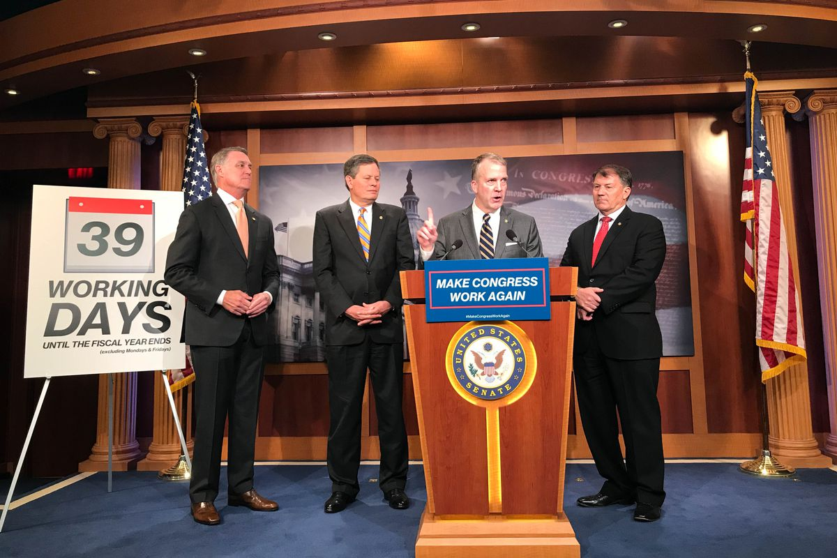 Alaska Sen. Dan Sullivan (at the podium) speaks at a press conference Tuesday held by Republican senators who want to urge their own party leadership to work weekends and during holiday breaks to pass a comprehensive budget and manage a backlog of Trump administration nominees. From left: Sen. David Perdue, R-Ga.; Sen. Steve Daines, R-Mont.; Sullivan; and Sen. Mike Rounds, R-S.D. (Erica Martinson / ADN)