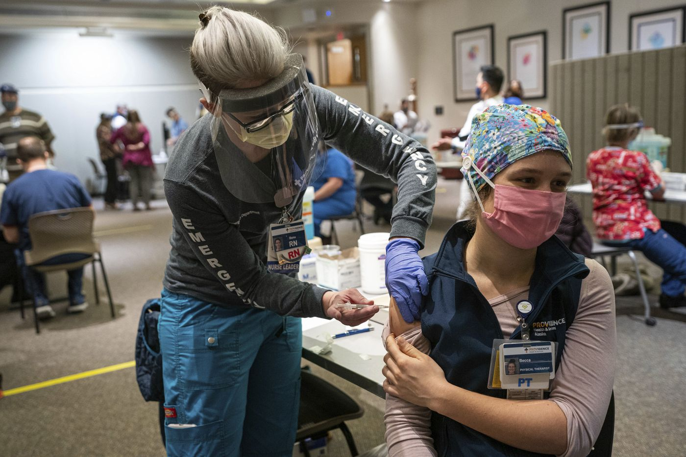 DECEMBER 16. Registered Nurse Banu Mufale administers a Pfizer-BioNtech COVID-19 vaccine to physical therapist Becca Mamrol, at Providence Alaska Medical Center. The hospital, Alaska's largest, plans to vaccinate 485 people this week. (Loren Holmes / ADN)
